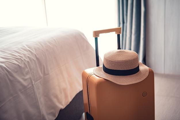 Saco de bagagem com chapéu em um quarto de hotel.