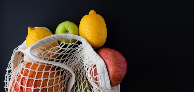 Saco de barbante branco com frutas em fundo preto. conceito de compras de desperdício zero