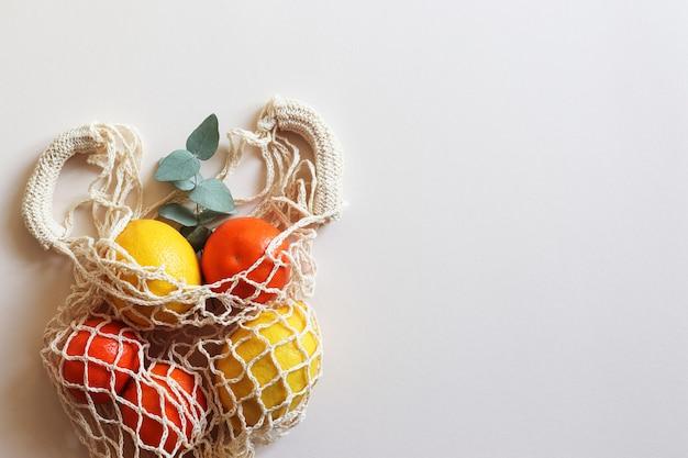 Saco de barbante ecológico com limões e tangerinas na mesa bege claro