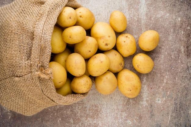 Saco de batatas frescas cruas em fundo de madeira, vista superior.