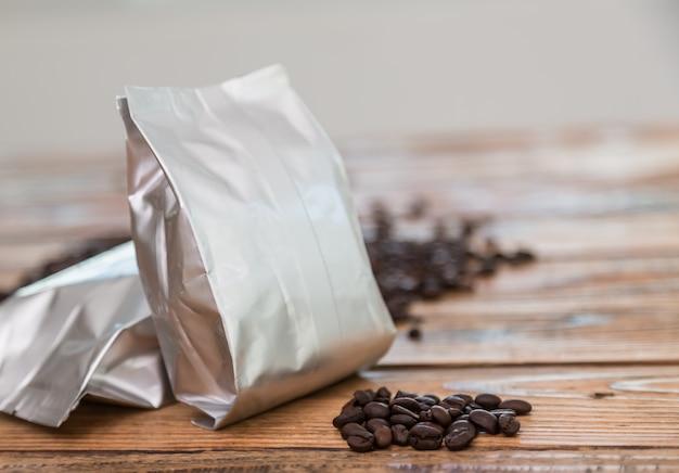 Saco de café metálica com grãos de café atrás