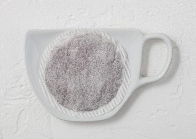 Saco de chá preto na placa de cerâmica com forma de xícara na luz de fundo.
