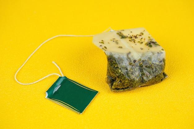 Saco de chá usado em fundo amarelo
