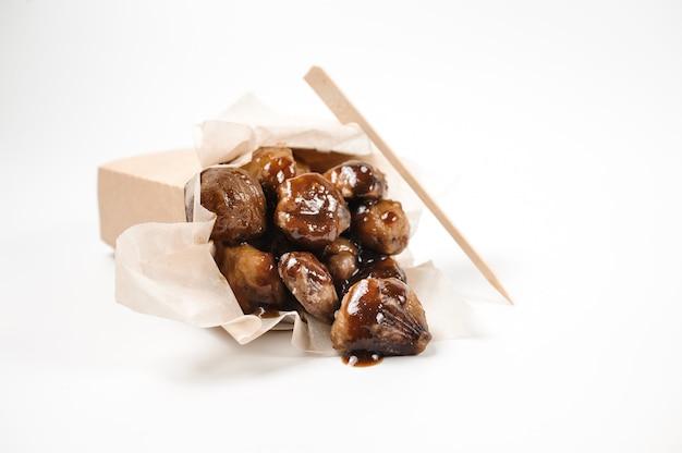 Saco de comida de papel isolado cheio de castanhas saborosas com molho