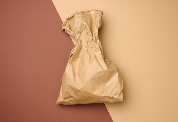 Saco de comida descartável completo de papel pardo em um fundo bege, conceito de entrega e pedido