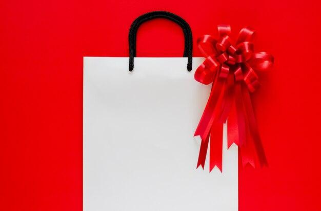 Saco de compra branco com laço vermelho e fita vermelha.