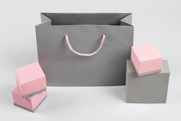 Saco de compra de papel cinza e caixas de presente rosa sobre fundo claro. espaço livre para texto. conceito de compra, venda, surpresa ou presente.