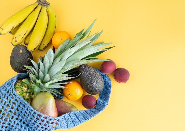 Saco de compra tecido azul com frutas sortidas em fundo amarelo. copie o espaço.