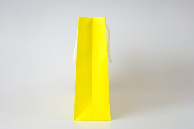 Saco de compras amarelo um fundo branco e cópia espaço para texto simples ou produto