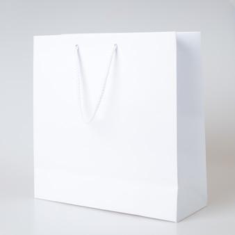 Saco de compras branco um fundo branco e cópia espaço para texto simples ou produto