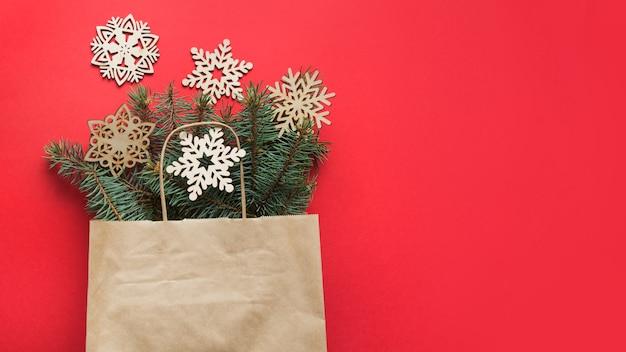 Saco de compras com decoração de flocos de neve diy esculpidos em madeira de natal e galhos de pinheiros no espaço vermelho