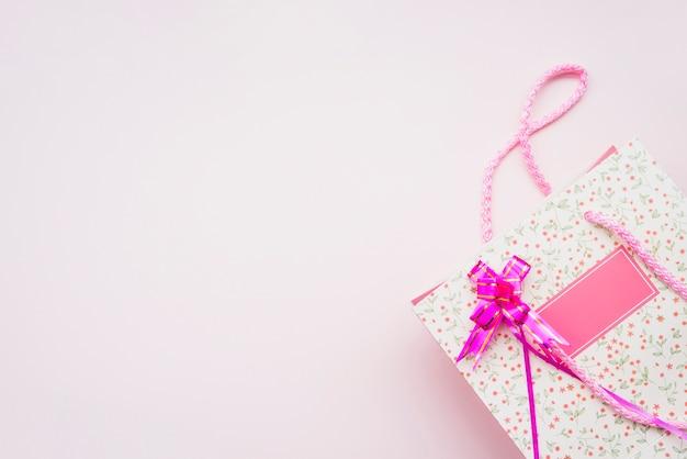 Saco de compras de aniversário com laço rosa no fundo rosa