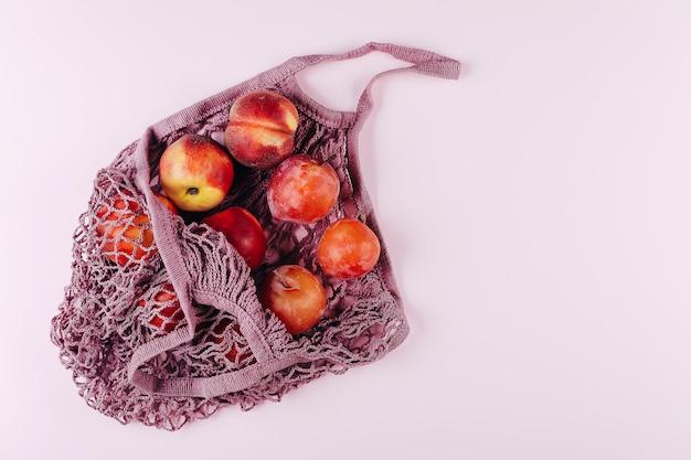 Saco de compras de malha com frutas plims e pêssego rosa. vista superior, configuração plana, espaço de cópia.