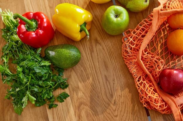 Saco de compras de malha eco com frutas e vegetais vegan saudáveis na cozinha em casa, conceito de alimentação saudável vegetariana.