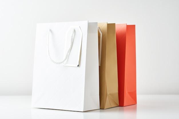 Saco de compras de papel três colorido sobre um fundo branco