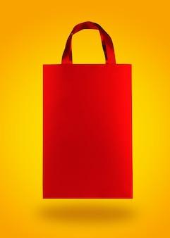 Saco de compras de papel vermelho sobre fundo amarelo