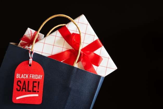 Saco de compras de venda de sexta-feira negra e caixas de presentes com tag de mensagem.