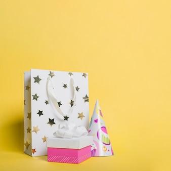 Saco de compras em formato de estrela; chapéu de papel e caixa de presente em fundo amarelo