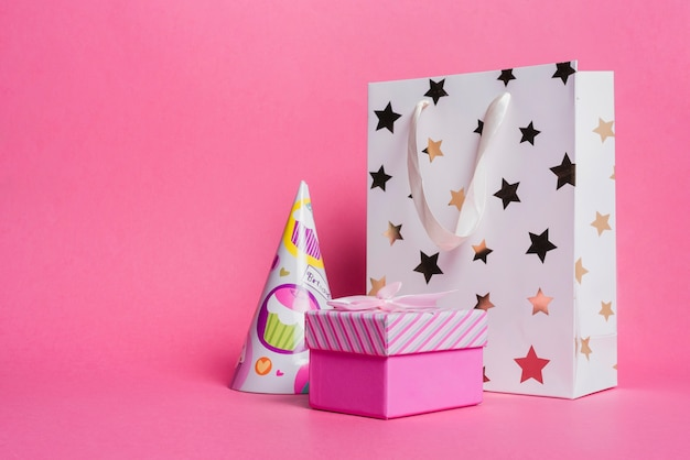 Saco de compras em formato de estrela; chapéu de papel e caixa de presente no fundo rosa