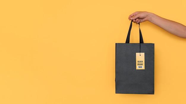 Saco de compras preto de sexta-feira em fundo amarelo de espaço de cópia