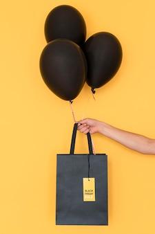 Saco de compras preto e balões