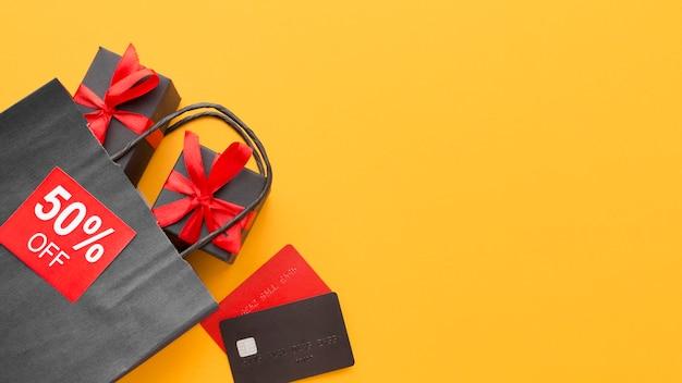 Saco de compras preto e caixas de presente copiam espaço