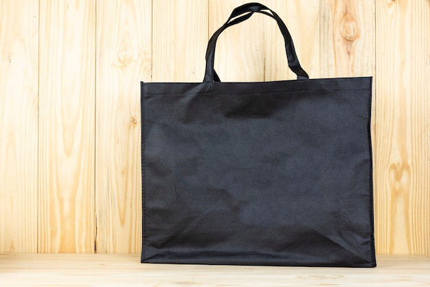 Saco de compras preto ou saco preto na mesa de madeira.