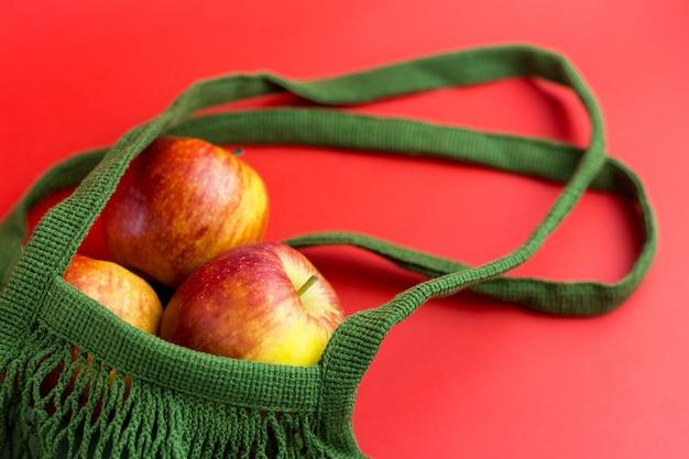 Saco de compras verde reutilizável com maçãs frescas.