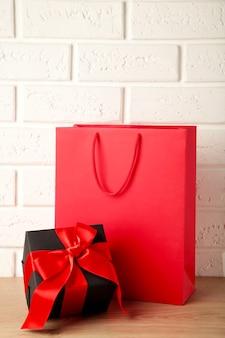 Saco de compras vermelho com presente sobre fundo claro. sexta-feira preta. vista do topo