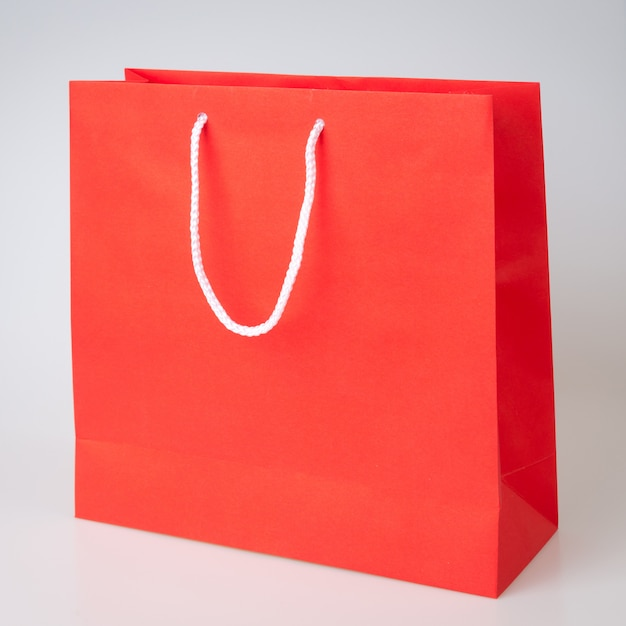 Saco de compras vermelho um fundo branco e cópia espaço para texto simples ou produto