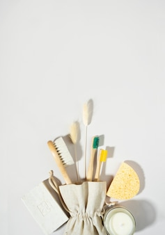 Saco de concept.linen de desperdício zero, escovas de dentes de bambu, vela de cera de soja no vidro. sombras da moda, fundo cinza claro. lagurus flores secas. sabonete artesanal. estilo de vida ecológico e sustentável. copie o espaço