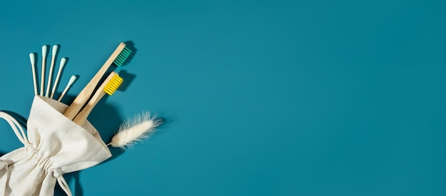 Saco de concept.linen de desperdício zero, palito de orelha. escovas de dentes de bambu, sombras da moda, fundo azul-marinho. lagurus flores secas. estilo de vida ecológico e sustentável. copie o espaço. banner extra largo.