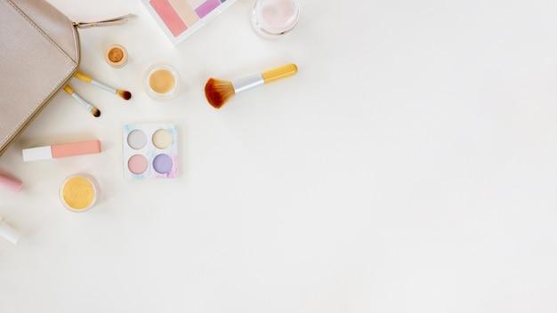 Saco de cópia-espaço com cosméticos na mesa