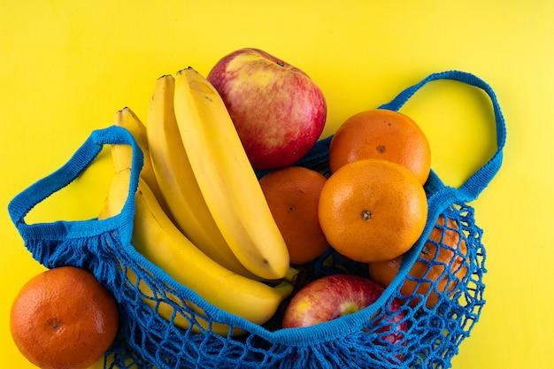 Saco de corda azul com bananas, maçãs vermelhas e tangerinas