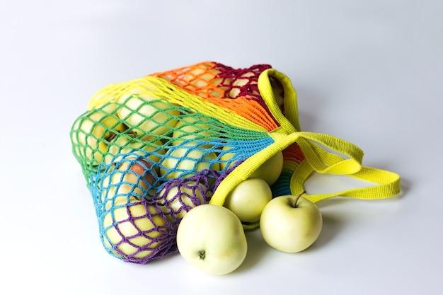 Saco de cordão de algodão reutilizável para compras com maçãs verdes, cores da moda do arco-íris multicolorido. encontra-se sobre uma mesa de luz. o conceito de desperdício zero, sem plástico