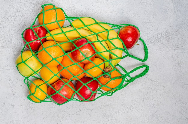 Saco de cordas com frutas mistas: bananas, limões, maçãs, laranjas.