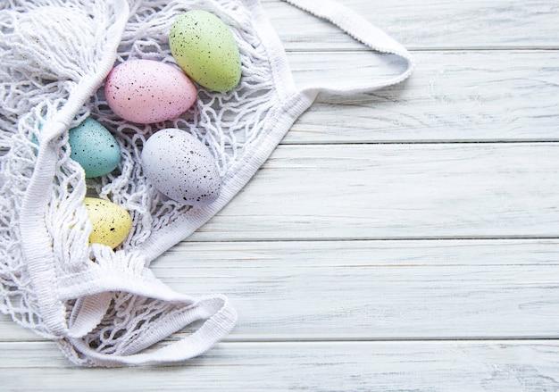 Saco de cordas com ovos de páscoa e flor de primavera no canto de uma mesa de madeira rústica