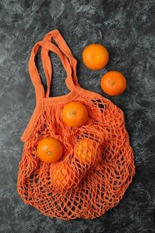 Saco de cordas com tangerinas em fundo preto esfumaçado