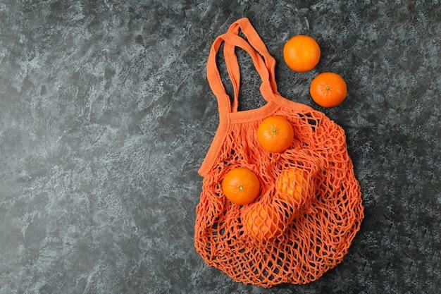 Saco de cordas com tangerinas em superfície preta esfumada