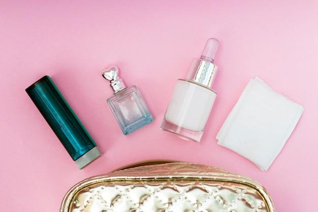 Saco de cosmético ouro sobre um fundo rosa close-up, copie o espaço