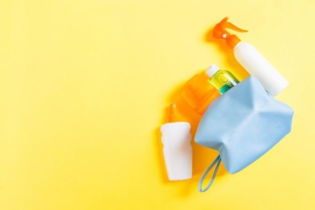 Saco de cosméticos feminino cheio de spray solar, protetor solar, protetor solar e loção para o corpo e creme spf em amarelo