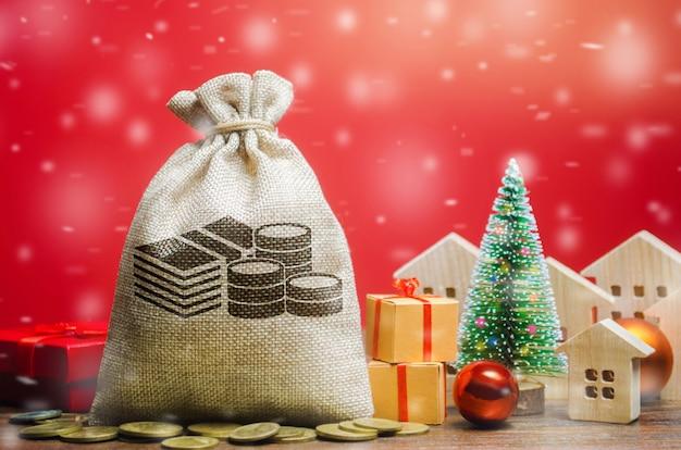 Saco de dinheiro, casas de madeira, árvore de natal e presentes. venda de imóveis de natal.