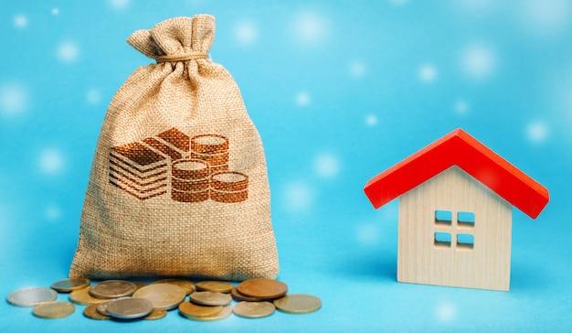 Saco de dinheiro com moedas e uma casa de madeira com neve. mercado imobiliário na temporada de inverno.
