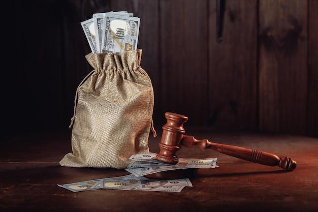 Saco de dinheiro com notas de dólar e martelo dos juízes resolução de disputas litígio resolução de conflito de interesses