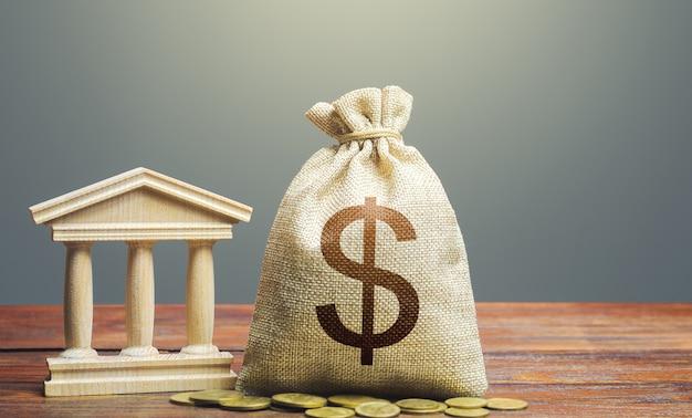 Saco de dinheiro do dólar e edifício do governo do banco. arrecadação e orçamentação de impostos. dívida do estado.