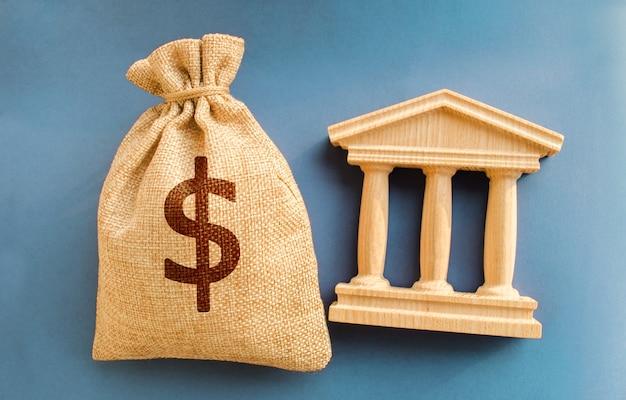 Saco de dinheiro em dólares e edifício do governo conceito de negócios e finanças