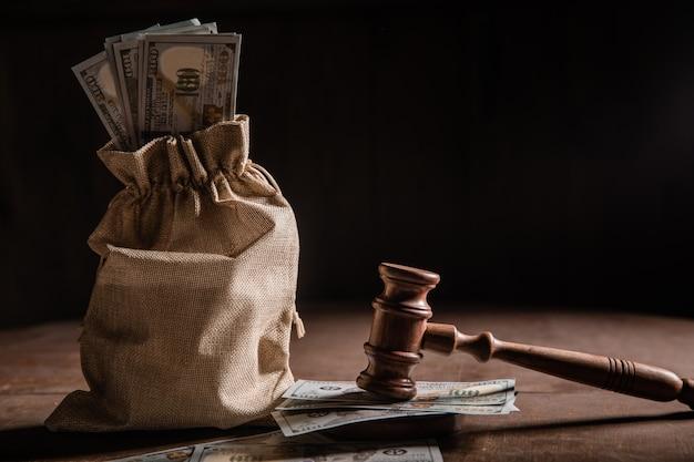 Saco de dinheiro em dólares e martelo dos juízes