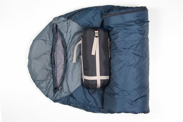 Saco de dormir dobrado sobre uma superfície branca. artigos para turismo e camping