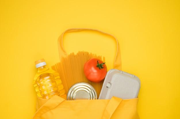 Saco de eco têxtil amarelo com compras. compras de produtos