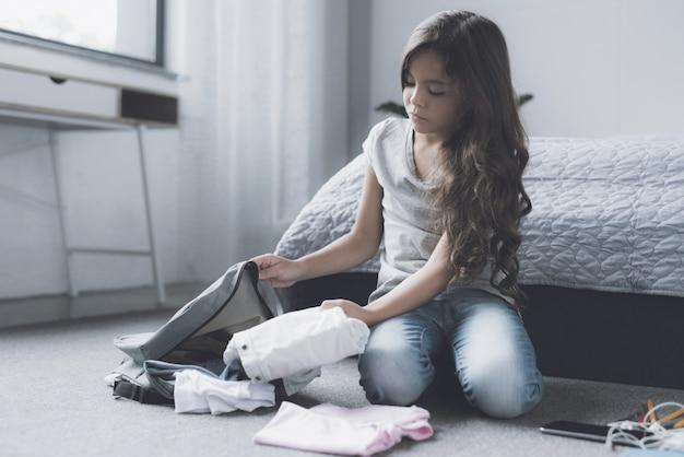 Saco de embalagem de menina bonita sentada no chão no quarto